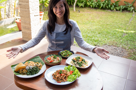 woman presenting various indonesian food