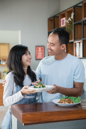 asian couple in the kitchen preparing food