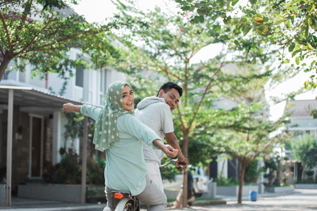 muslim couple riding a bike