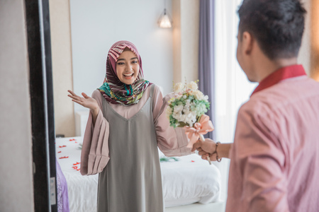 muslim woman having a flower from man Stock Photo