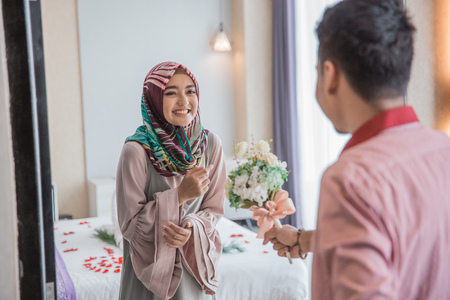 muslim woman receiving flower from her husband