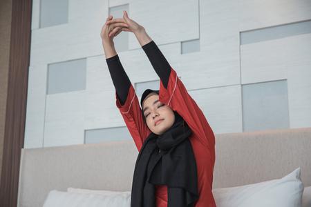 donna musulmana asiatica che allunga il braccio
