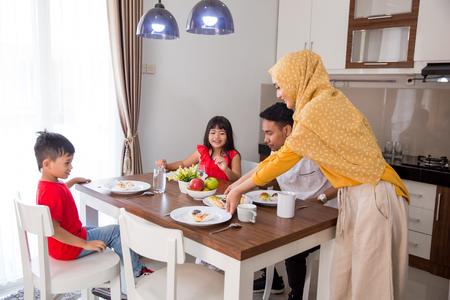 familia musulmana asiática desayunando