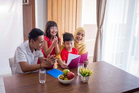 leyendo un libro con los padres Foto de archivo