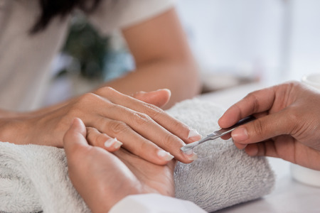 Beautician using a cuticle pusher to give a nail manicure Stock Photo