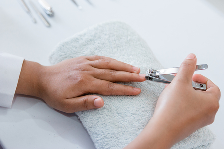 A woman hand manicure with nail clipper