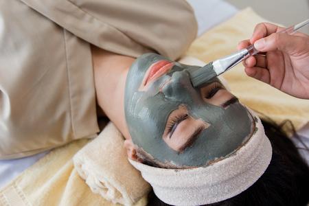 Bild der Kosmetikerin, die Gesichtsmaske tut Standard-Bild