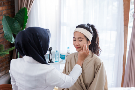 Cosmetic doctor examining female client