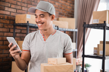man with package holding smartphone