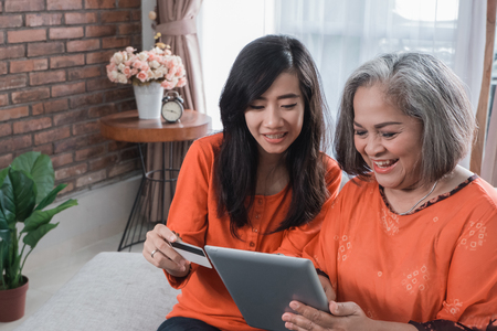 woman using tablet with her mature mom