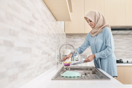 beautiful young woman wearing hijab washing the dishes