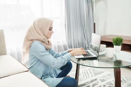 美丽的家庭主妇戴着头巾在家用笔记本电脑工作