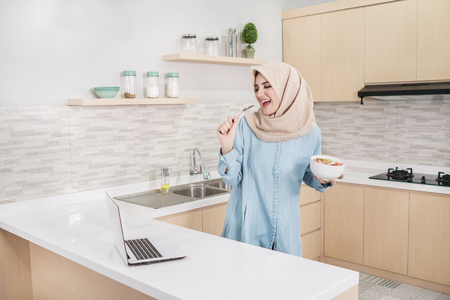 beautiful young woman wearing hijab eating a bowl of granola wit