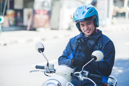 tassista del motociclo che indossa i guanti per la guida in sicurezza Archivio Fotografico