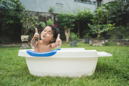 happy beautiful baby girl take a bath in a baby bath tube while Standard-Bild - 108150740