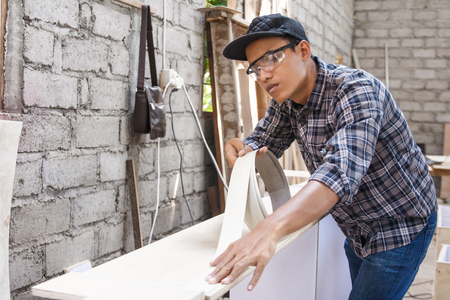 young carpenter applying wood vinyl into a furniture Stok Fotoğraf