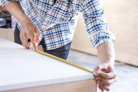young carpenter measuring the furniture Stok Fotoğraf