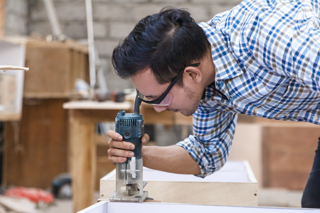 worker cutting the edge of wood board using fret saw Stock Photo