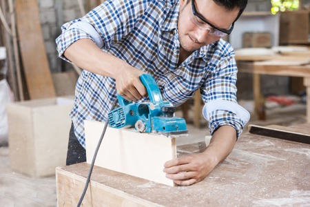worker at carpenter workspace cutting the surface of furniture u Stok Fotoğraf
