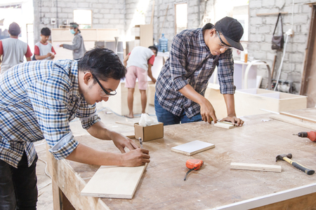 young carpenter measuring and marking the wood board 스톡 콘텐츠