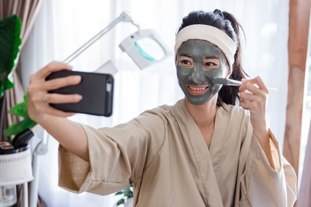 Young woman selfie when using facial mask mud