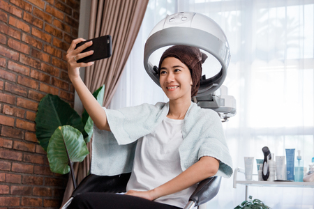 woman taking selfie while getting treatment Stockfoto