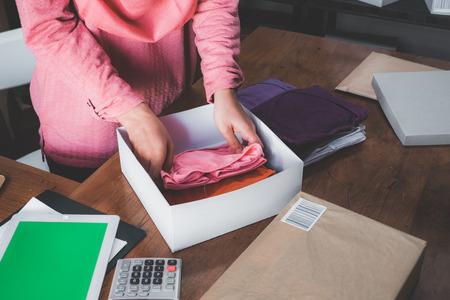 muslim asian woman online ecommerce entrepreneur preparing product to be shipped Banco de Imagens