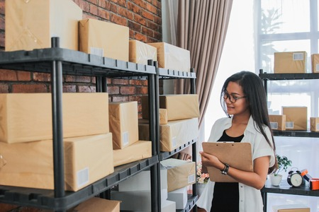 Young woman checking packages with the clipboard Stock Photo