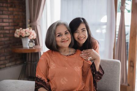 reife Mutter und ihre erwachsene Tochter lächeln Standard-Bild