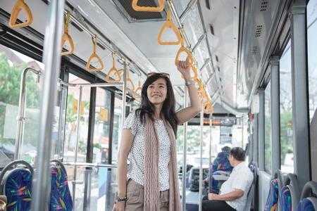 fille asiatique debout sur le bus