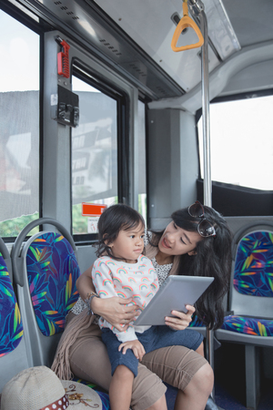 asian woman is holding her daughter and showing tablet Stock Photo - 109905250