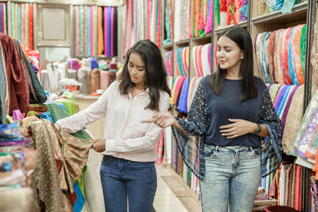 two young woman shoppic at fabric shop