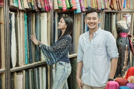 young woman and a man shopping at fabric shop Stock fotó