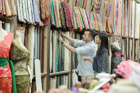 a cloth shop employee serves his customers