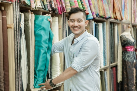 young man choosing material for clothes