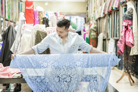 a fabric shop employee roll up the material fabric