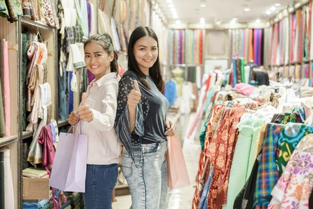 two young woman with shopping bag giving thumbs up