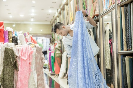 a fabric shop employee cutting material using scissors