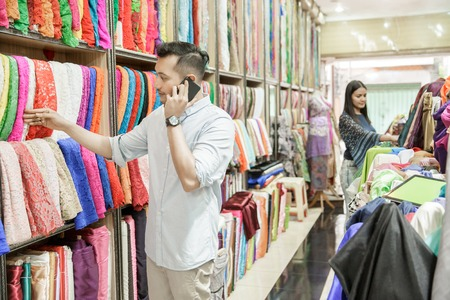young man choosing material for clothes while talking on mobilep Stock fotó