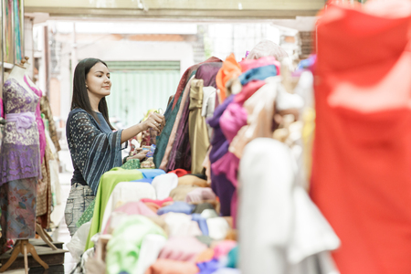 two young woman shopping at fabric store