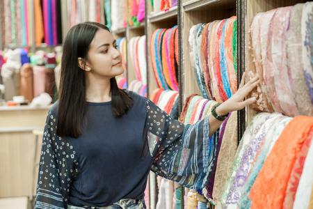 beautiful woman looking around fabric at fabric store Stock fotó