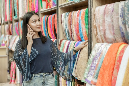 beautiful woman talking on mobilephone while looking around fabr