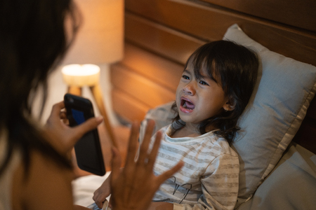 Mother warning little girl not to more play game Imagens