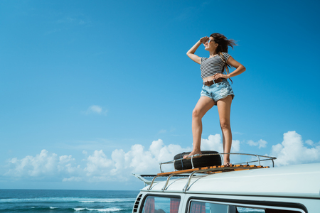 Beautiful woman enjoy road trip nature standing on the roof