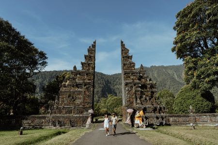 couple running together through bali traditional gate Foto de archivo