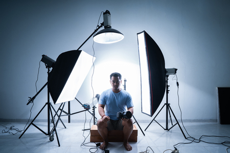 male photographer in photography studio surrounded by lighting equipment 写真素材