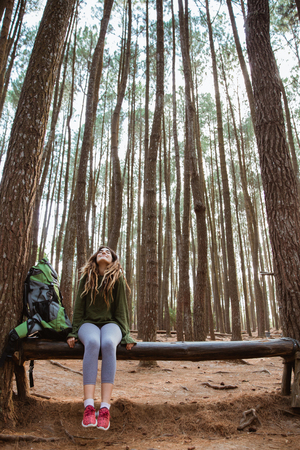 young woman hiker relaxing in the woods Stock Photo