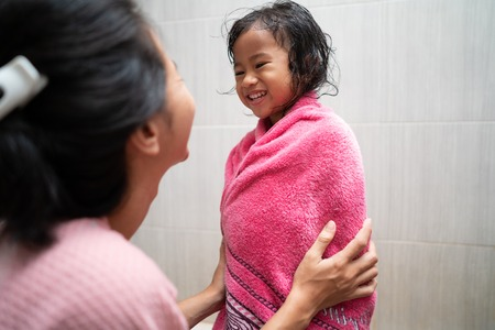kid being dry by her mom using towel