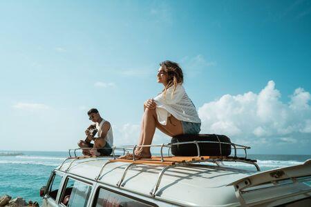 junge Leute auf dem Dach eines Minivans im Retro-Stil, die Zeit miteinander genießen? Standard-Bild