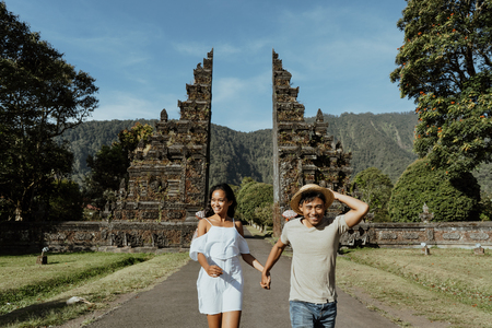 couple running together through bali traditional gate Stock Photo